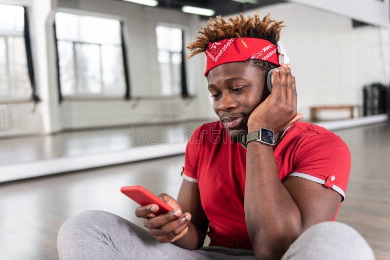 Angenäm le lyssnande musik för kort-haired grabb till och med hörlurar arkivfoton