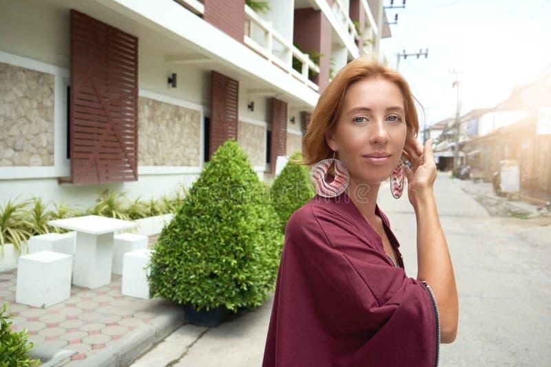 Angenäm ljust rödbrun kvinna som poserar på gatabakgrund royaltyfri fotografi