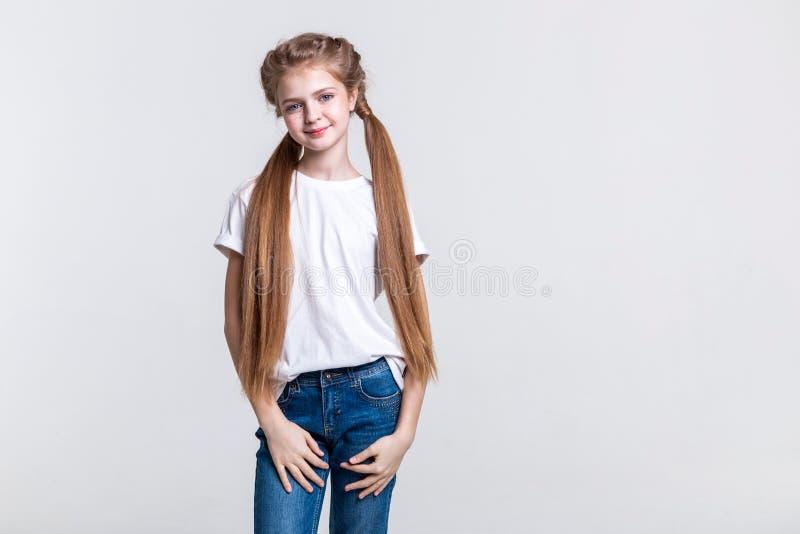 Angenäm lugna flicka som ler lätt, medan framlägga hennes extrahjälp-långa hår arkivfoto