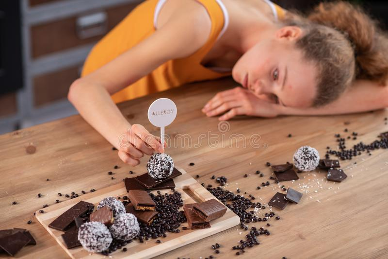Angenäm mager flicka som lutar på trätabellen med choklad på den royaltyfri bild