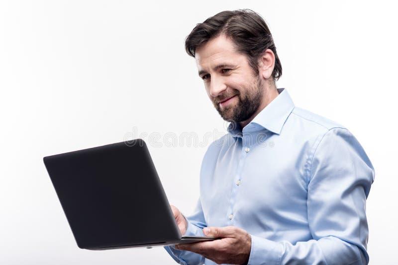 Angenäm medelålders affärsman som arbetar på hans bärbar dator fotografering för bildbyråer