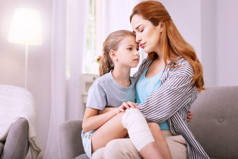 Angenäm röd haired kvinna som kramar hennes barn royaltyfria bilder