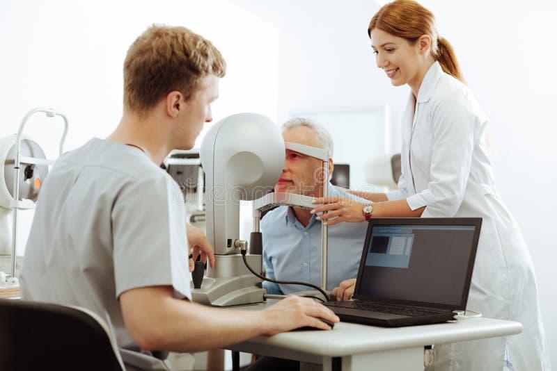 Angenäm sjuksköterska som hjälper den tålmodiga besöka ögonspecialisten royaltyfria foton
