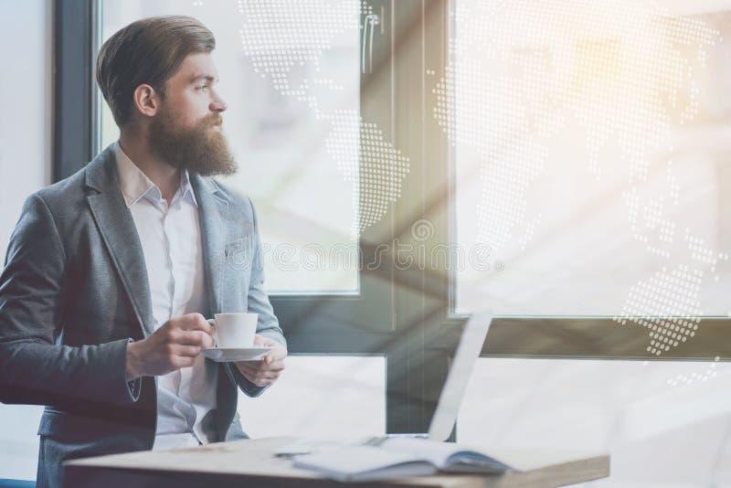 Angenäm skäggig man som dricker kaffe arkivbild