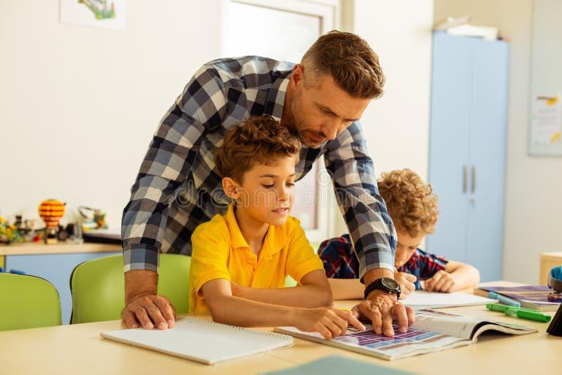 Angenäm smart pojke som lär hur man läser engelskt royaltyfri bild