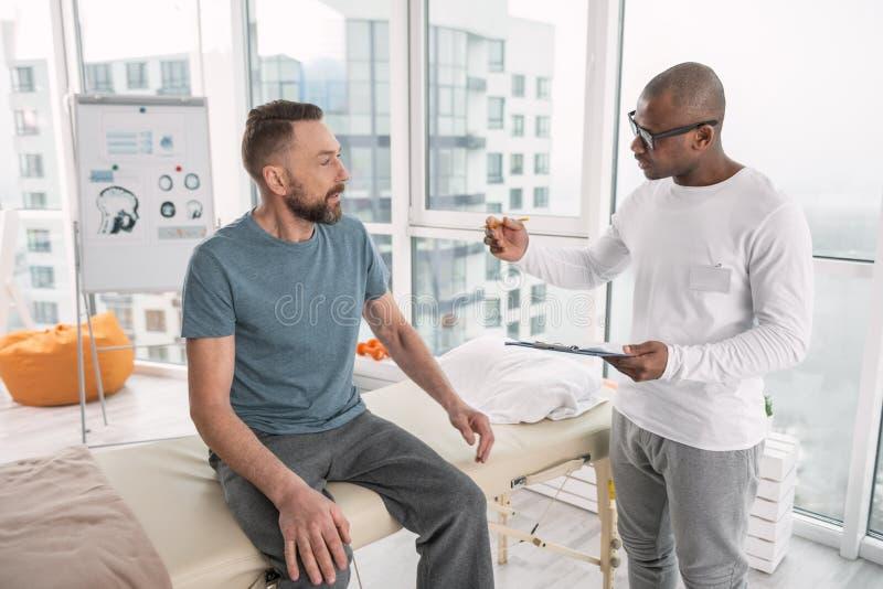 Angenäm smart terapeut som talar till hans patient arkivfoto