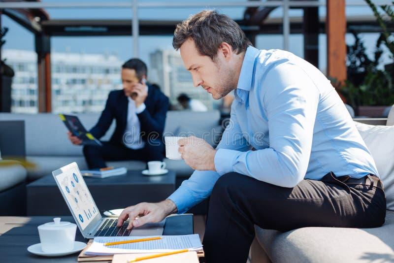 Angenäm trevlig affärsman som arbetar på en bärbar dator royaltyfria foton