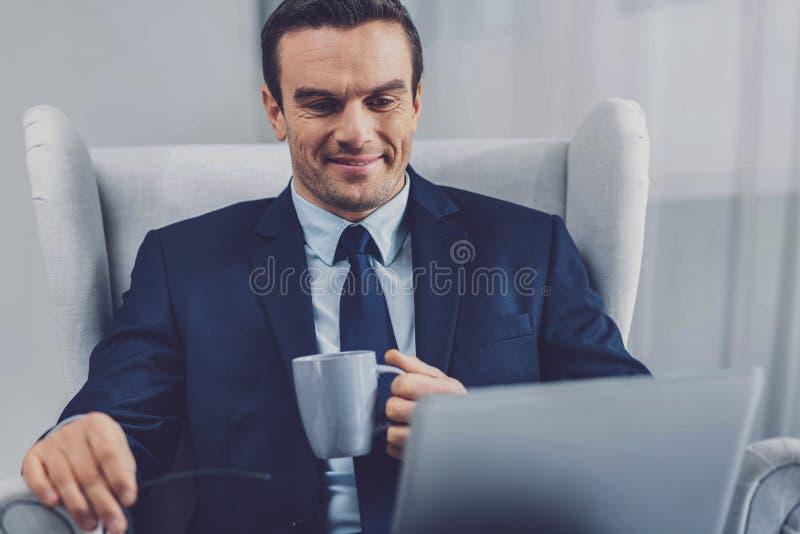Angenäm trevlig affärsman som rymmer en kopp te arkivfoto