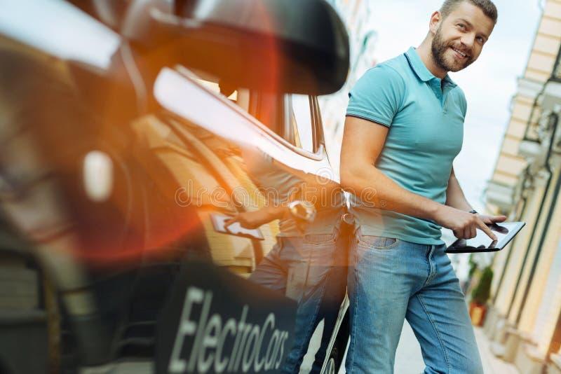 Angenäm ung man med ett minnestavlaanseende nära hans bil fotografering för bildbyråer