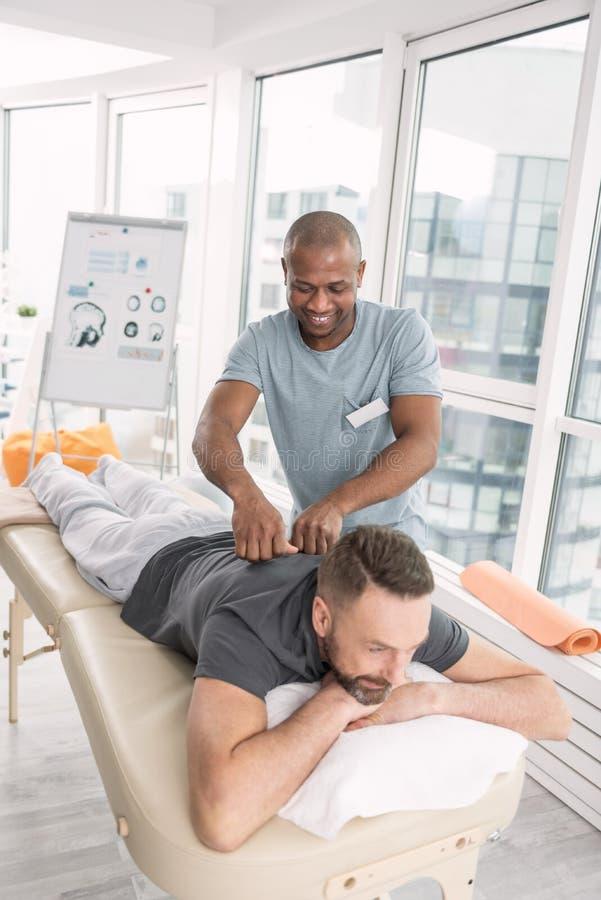 Angenäm vuxen man som har en massage arkivbilder