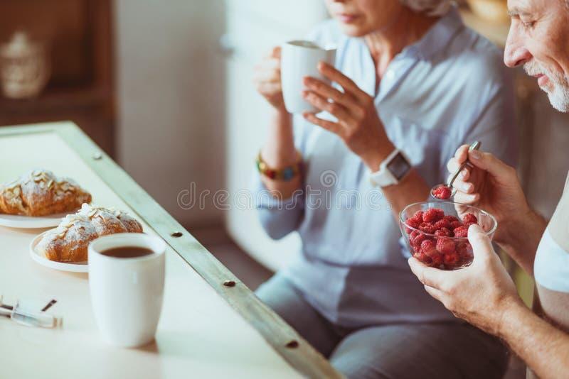 Angenäma åldriga par som har frukosten i köket royaltyfri bild