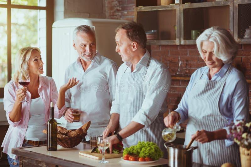 Angenäma åldriga par som lagar mat i köket royaltyfria bilder