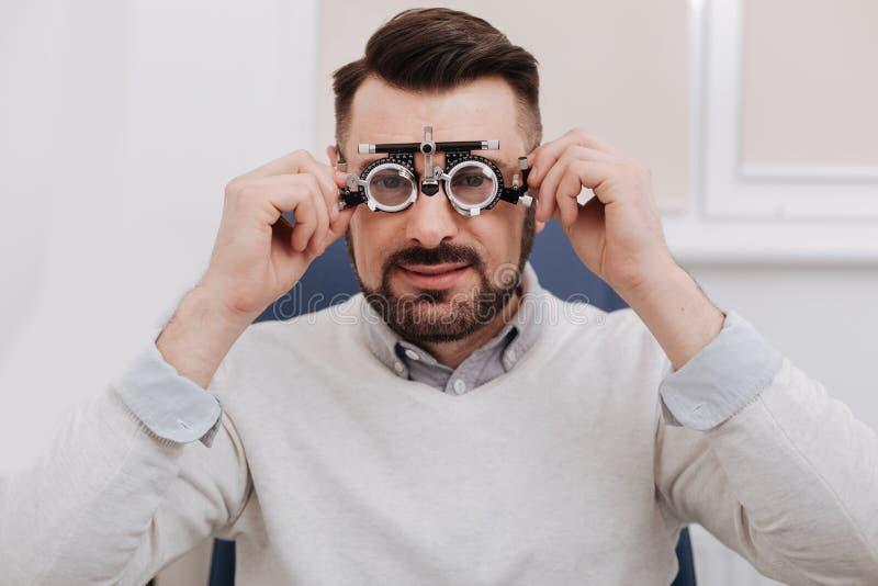 Angenäma bra seende för ögonundersökning för man hållande exponeringsglas royaltyfria foton