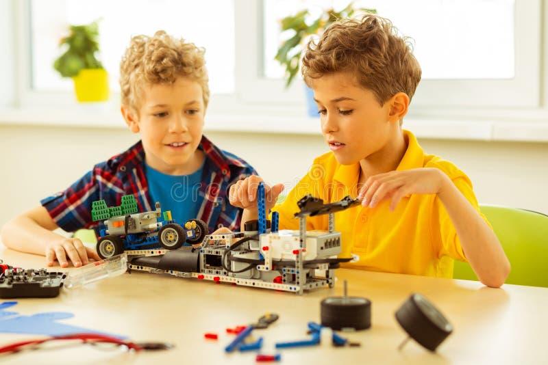 Angenäma gulliga pojkar som tillsammans sitter på skrivbordet arkivbilder