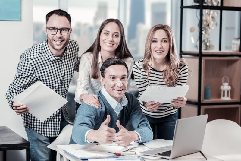 Angenäma lyckliga anställda som står nära tabellen och le royaltyfri bild