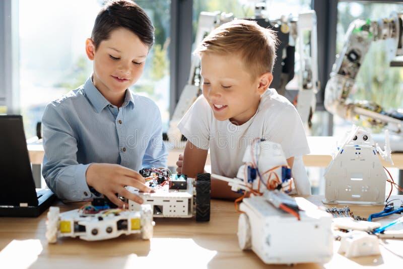 Angenäma små ungar som tillsammans skapar robotar arkivbild