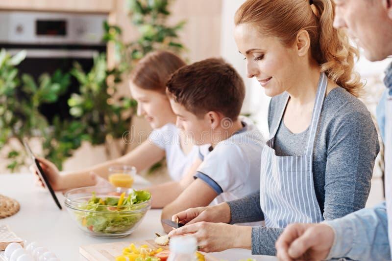 Angenämt älska uppfostrar matlagningsallad för deras barn royaltyfria foton