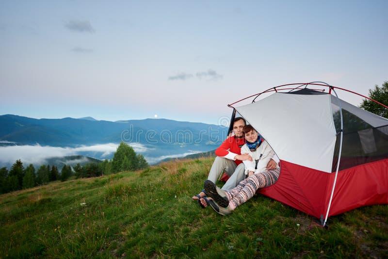 Angenämt krama för par sitter i tält mot landskap av väldiga Carpathian berg royaltyfria bilder