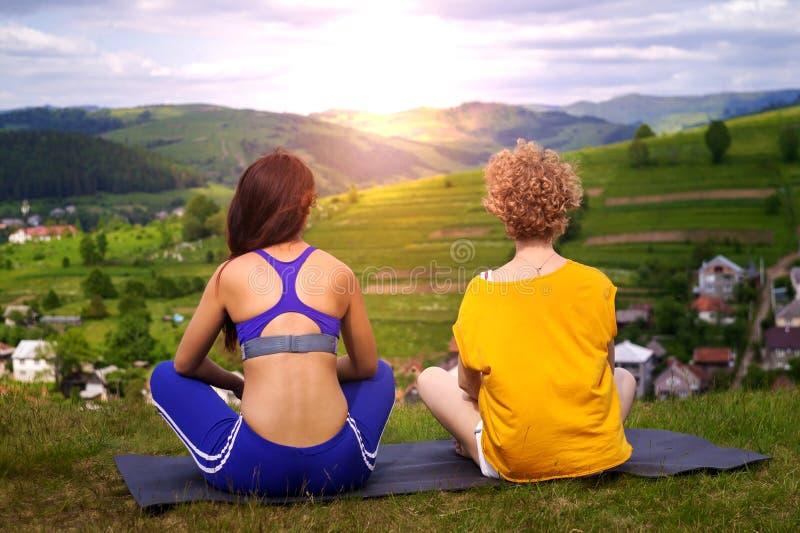 Angen?m kommunikation Lycklig förtjust ung kvinna som ler och talar till hennes vän, medan sitta på matt yoga royaltyfria bilder
