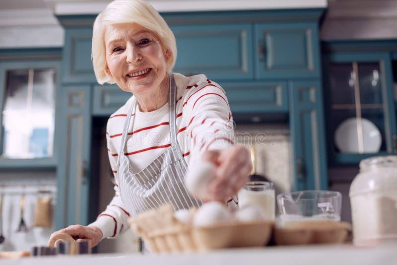 Angenehme ältere Frau, die Ei bei der Herstellung des Teigs nimmt lizenzfreies stockbild