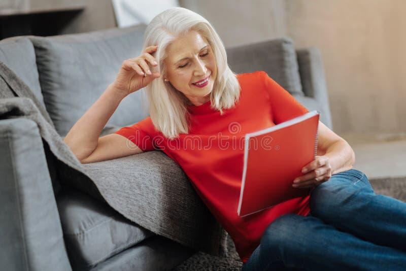 Angenehme ältere Frau, die ein Notizbuch hält lizenzfreies stockfoto