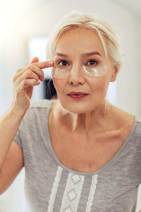 Angenehme ältere Frau, die ihr Gesicht im Spiegel betrachtet stockfotografie