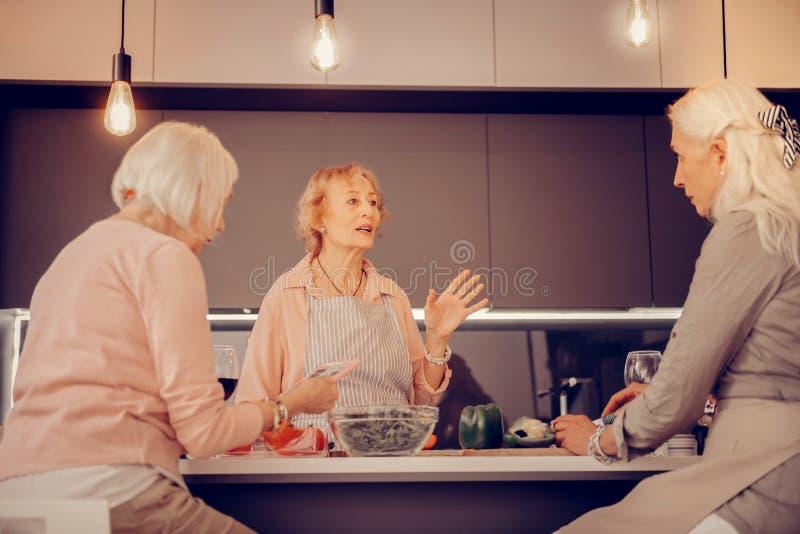 Angenehme ältere Frau, die mit ihren Freunden spricht lizenzfreie stockfotografie