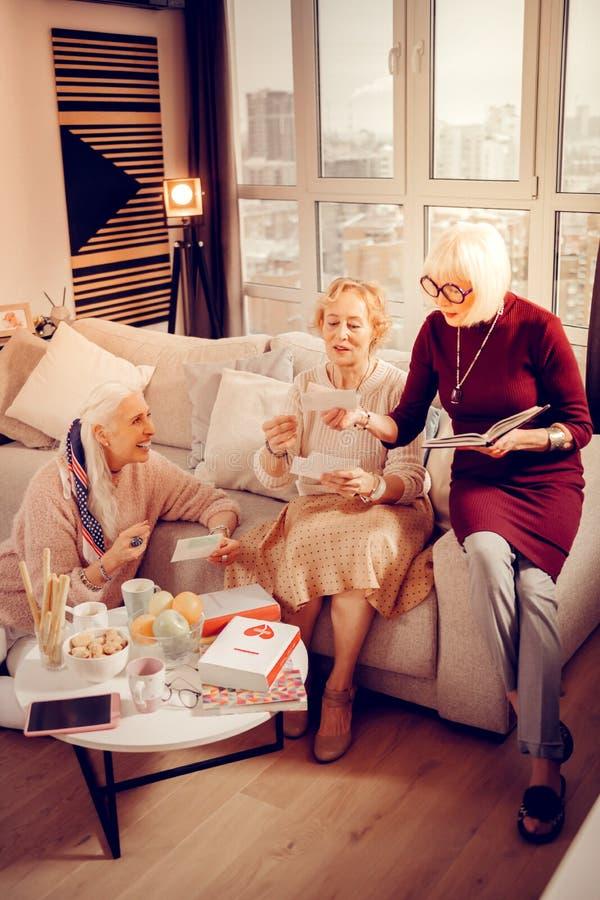 Angenehme ältere Frauen, die alte Fotos betrachten stockfotos