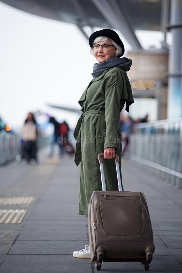 Angenehme alte Dame trägt Gepäck lizenzfreies stockbild