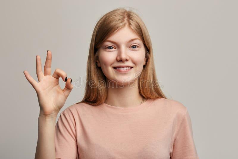 Angenehme aufgeregte Frau mit Vertretungs-O.K.zeichen des strahlenden Lächelns lizenzfreie stockfotos