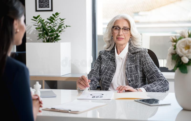 Angenehme Berufsfrauen arbeiten im Büro lizenzfreie stockfotografie