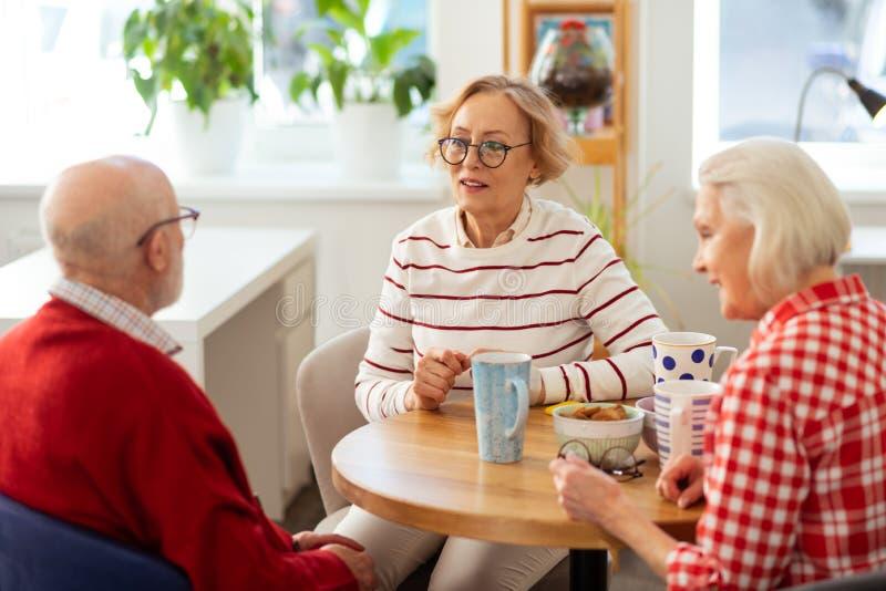 Angenehme gealterte Leute, die köstlichen Tee zusammen trinken stockbilder