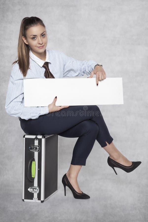 Angenehme Geschäftsfrau sitzt auf einem Koffer und hält ein commercia stockfotos