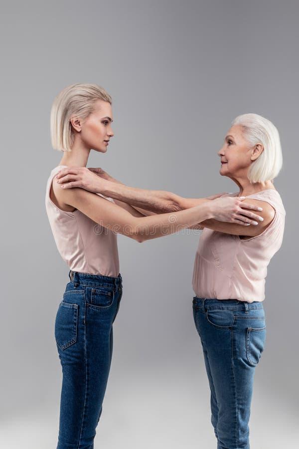 Angenehme grau-haarige ältere Dame, die ihre blonde schöne Tochter umarmt stockfotos