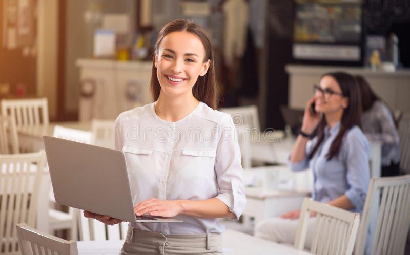 Angenehme lächelnde Frau, die Laptop hält lizenzfreie stockfotografie