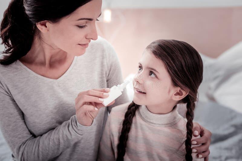 Angenehme Mutter, die ihrem Kind mit nasalen Tropfen hilft stockbilder
