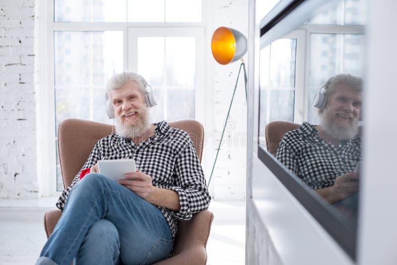 Angenehmer älterer lächelnder Mann beim Aufpassen des Films auf Tablette lizenzfreie stockfotos
