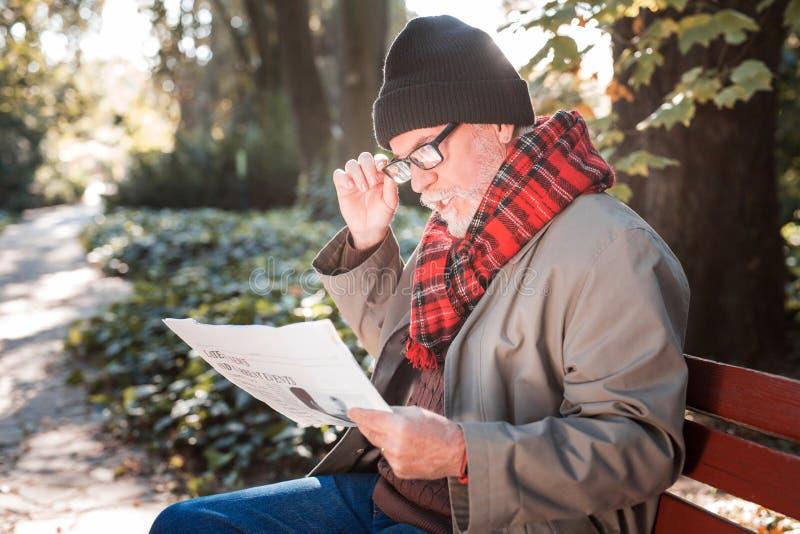 Angenehmer älterer Mann, der eine Morgenzeitung hält lizenzfreie stockfotos