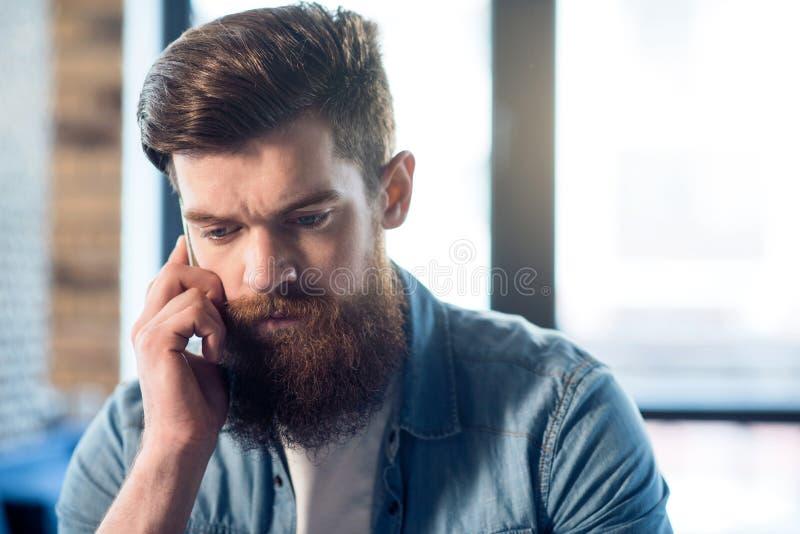 Angenehmer bärtiger Mann, der Handy verwendet lizenzfreie stockfotos