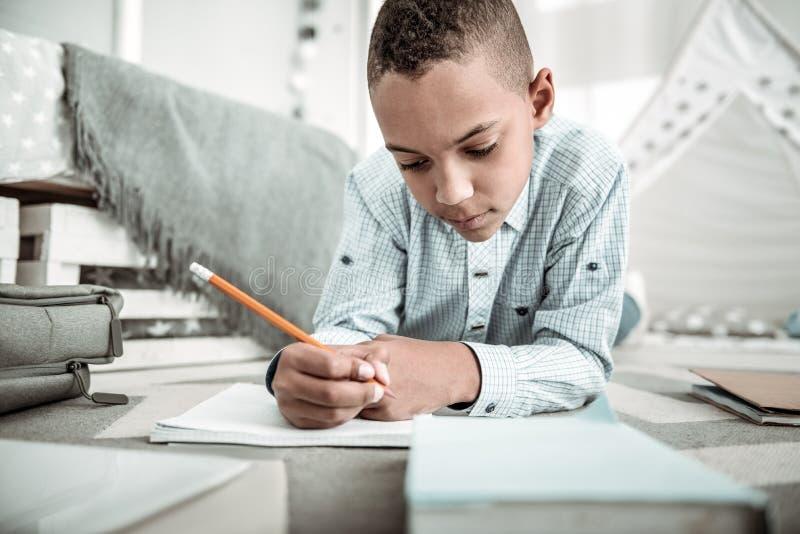 Angenehmer durchdachter Junge, welche nach einer Lösung zur Aufgabe sucht lizenzfreie stockbilder