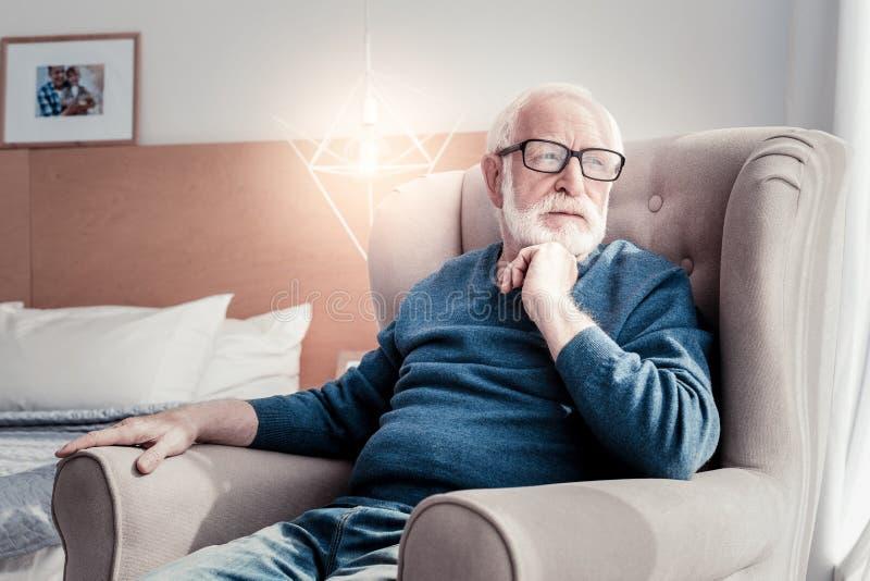 Angenehmer gealterter Mann, der sein Kinn berührt lizenzfreie stockbilder