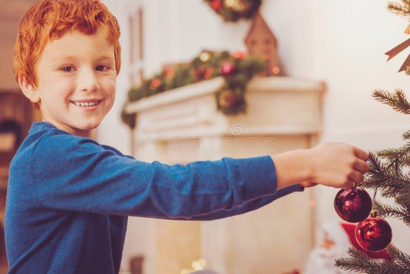 Angenehmer Ingwer-haariger Junge, der Weihnachtsbaum verziert stockfotos