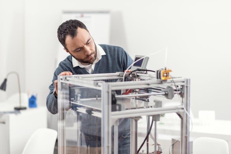 Angenehmer junger Mann, der die Arbeit des Druckers 3D überprüft stockbild