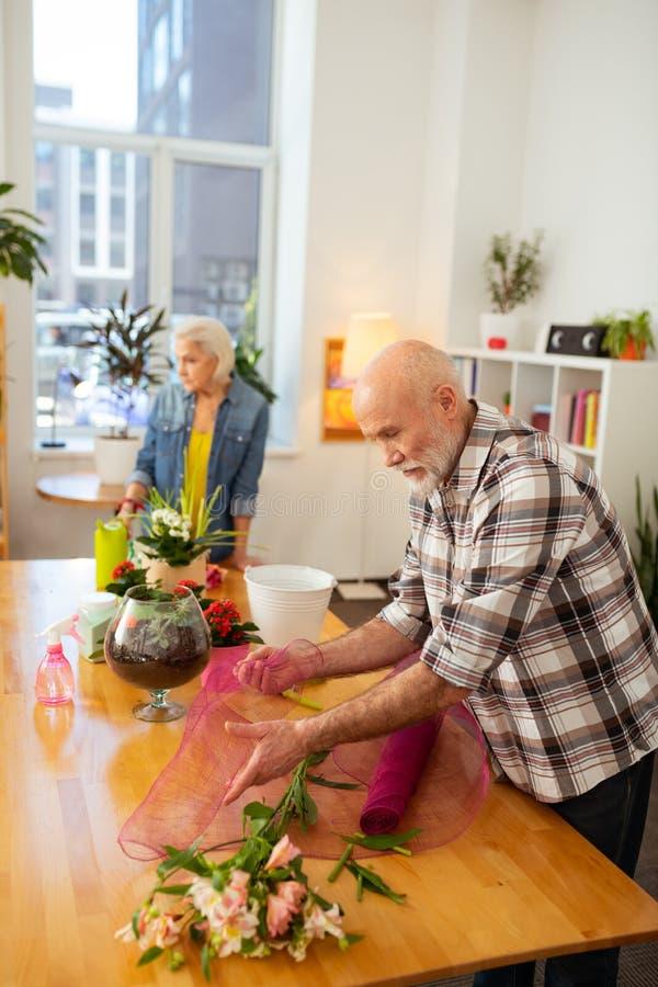 Angenehmer positiver gealterter Mann, der eine Blume einwickelt lizenzfreie stockbilder