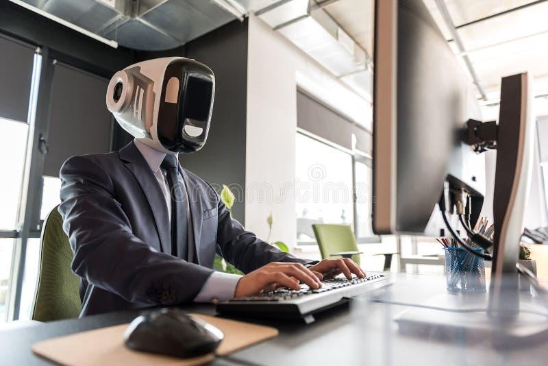 Angenehmer Roboter funktioniert mit Konzentration stockfoto