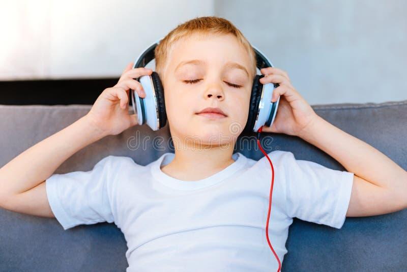 Angenehmer ruhiger Junge, der entspannt glaubt lizenzfreies stockfoto