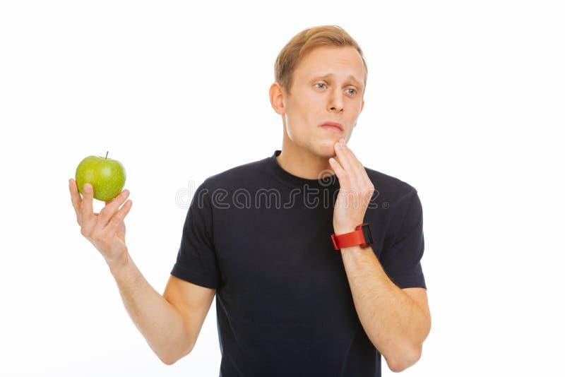 Angenehmer trauriger Mann, der einen grünen Apfel hält stockbild