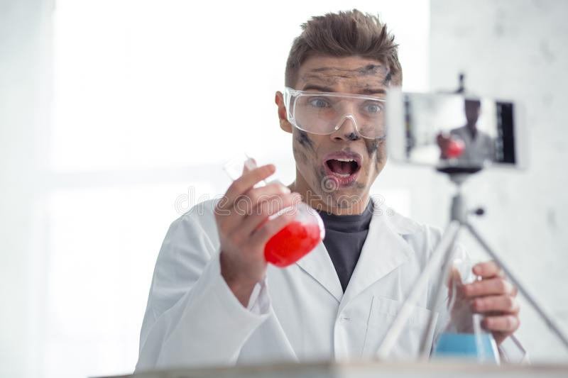 Irritated dirty blogger after the experiment. Anger. Attractive irritated fair-haired young blogger wearing uniform and holding test tubes and making new video royalty free stock image