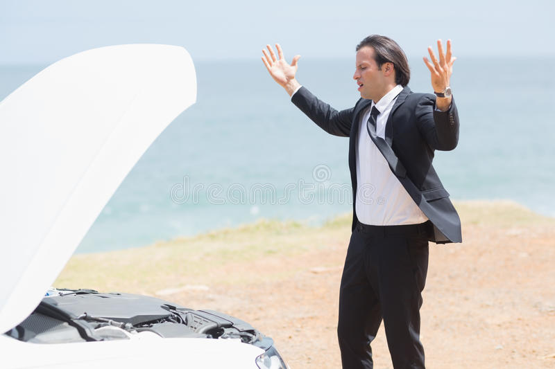 Anger businessman looking at engine. Of his car royalty free stock photos