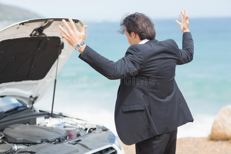 Anger businessman looking at engine. Of his car stock photo